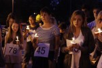 Attendees hold candles at the vigil.