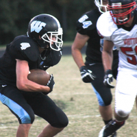 Running back Gunnar Morton braces for contact as he runs toward a Wootton defender. Photo by Nick Anderson.
