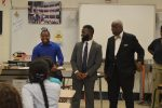 Two Phi Delta Sigma fraternity members presented English teacher Omari James with