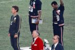 Tommie Smith (center) and John Carlos (right), protested racism in the United States by raising black gloved fists as the national anthem played during their medal ceremony at the 1968 Olympics. The U.S. Olympic Committee expelled Smith and Carlos from the Games as punishment for their actions. It was the first major race-related protest at a sporting event, paving the way for recent athletes' protests. Photo courtesy Wikimedia Commons.